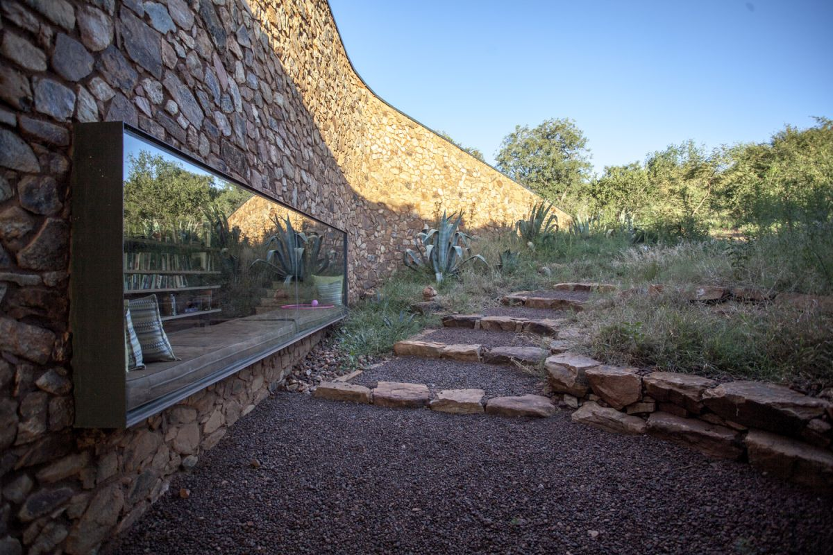 The house is framed by a series of rammed earth walls and several stone walls