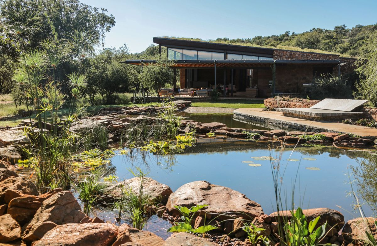 The large windows and openings frame the beautiful pond, the garden and the distant views