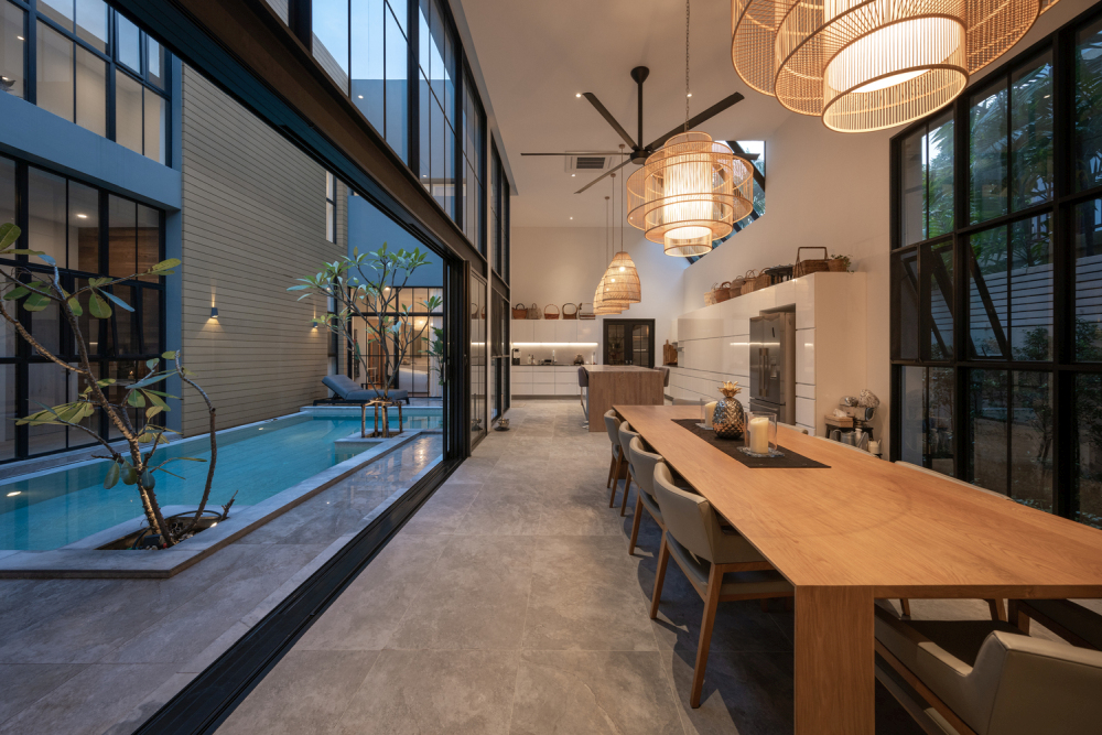 The kitchen and dining area are positioned on one side of the pool with sliding glass doors towards it