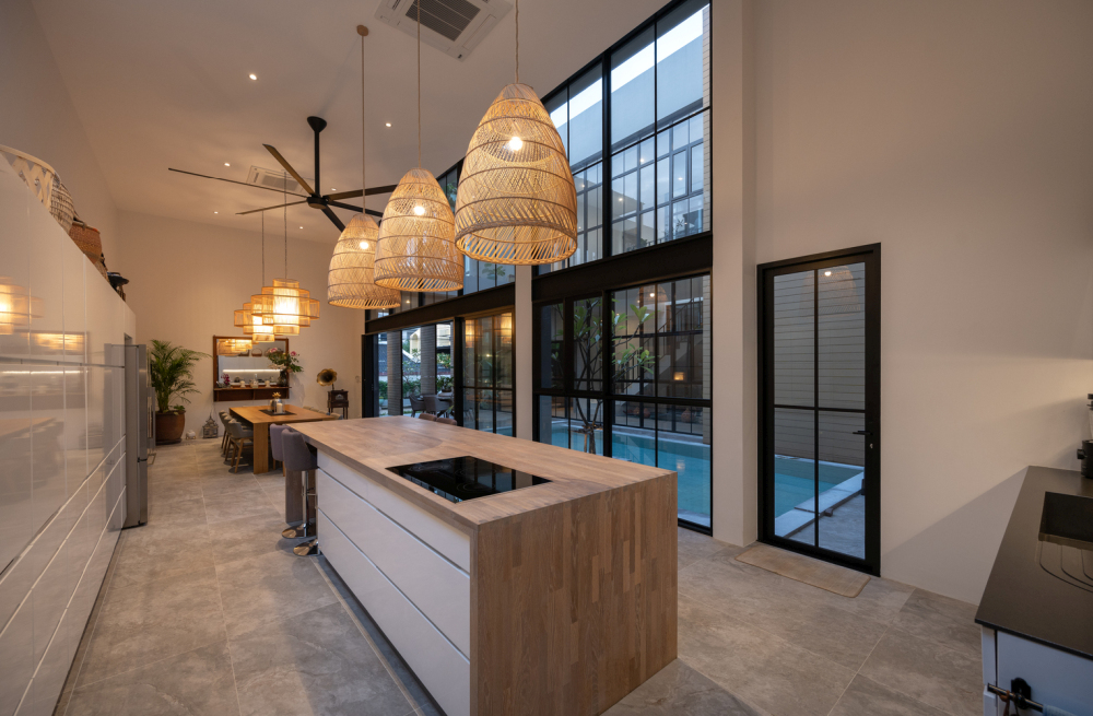 The high ceiling was ideal for these large [pendant lamps above the kitchen island and the dining table