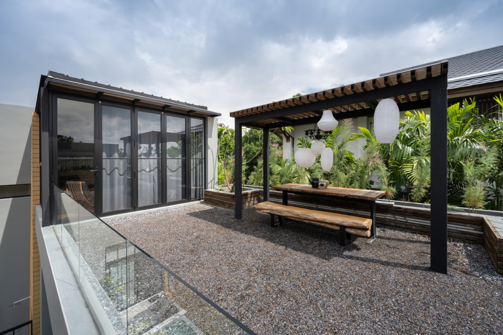 The roof terrace has glass railings and a covered sitting area with greenery