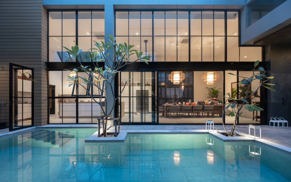 Small pockets of greenery complement the pool and terrace area
