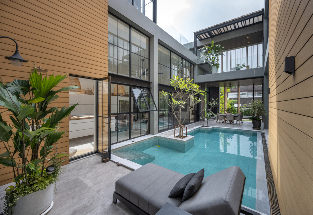 The swimming pool is positioned at the center of the house and surrounded by interior spaces