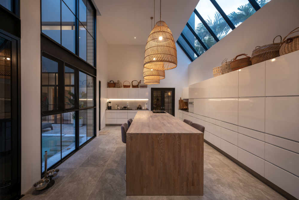 The kitchen is long and narrow, with angled clerestory windows, a big island and lots of storage