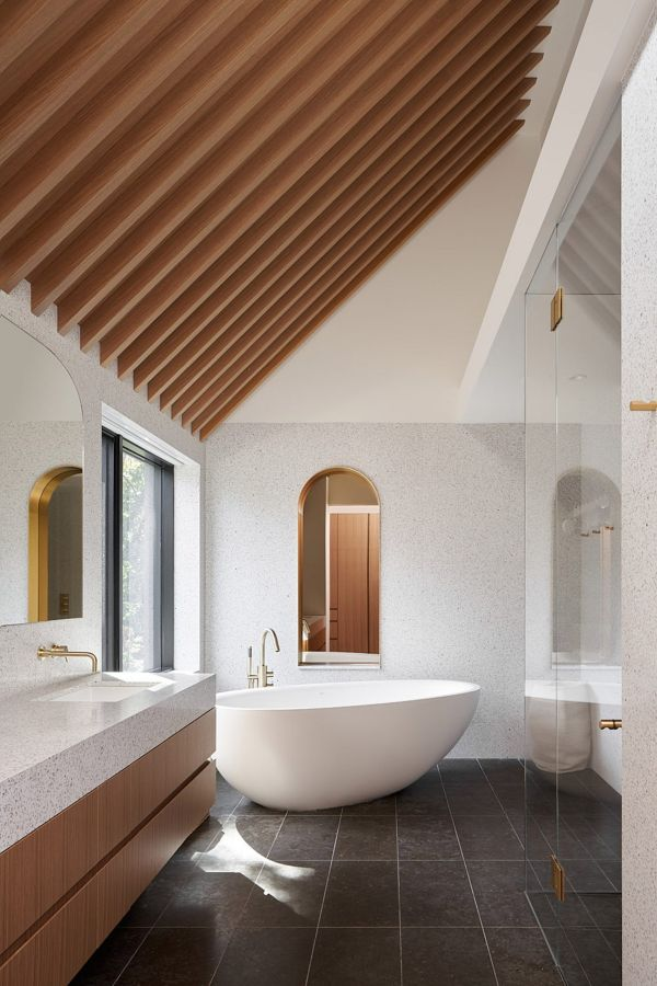 The top floor guest bathroom features elegant gold fixtures and an oval freestanding tub