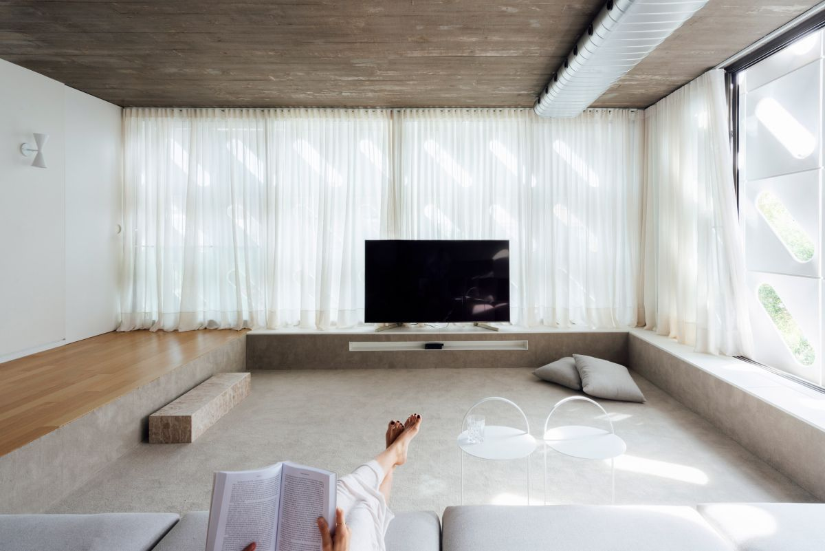 The sunken media room is a very cozy and airy space thanks to the large windows