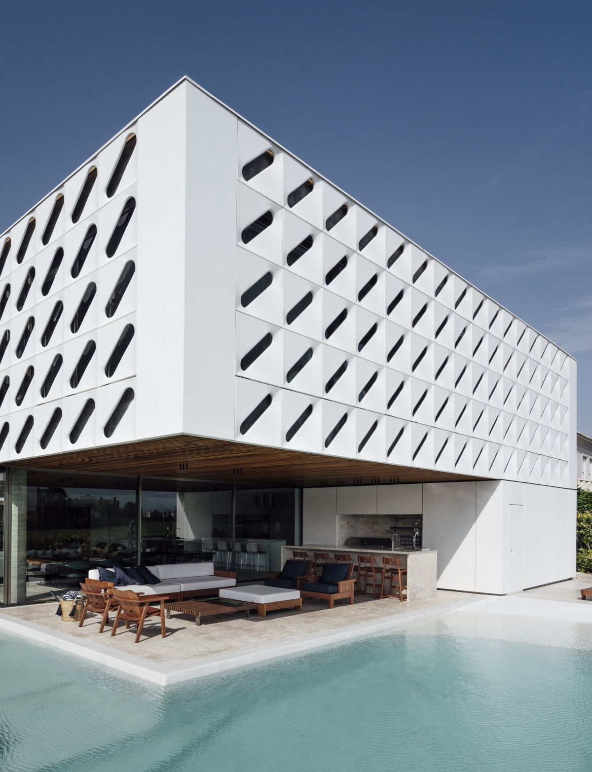 The L-shaped swimming pool wraps around the covered patio which serves as an extension of the indoor living area