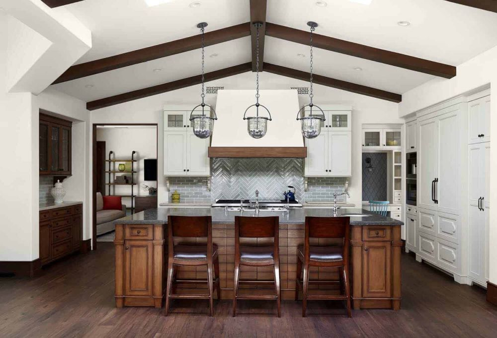 Exposed wooden beams on the kitchen ceiling create a cozy vibe and complement the floors and the island